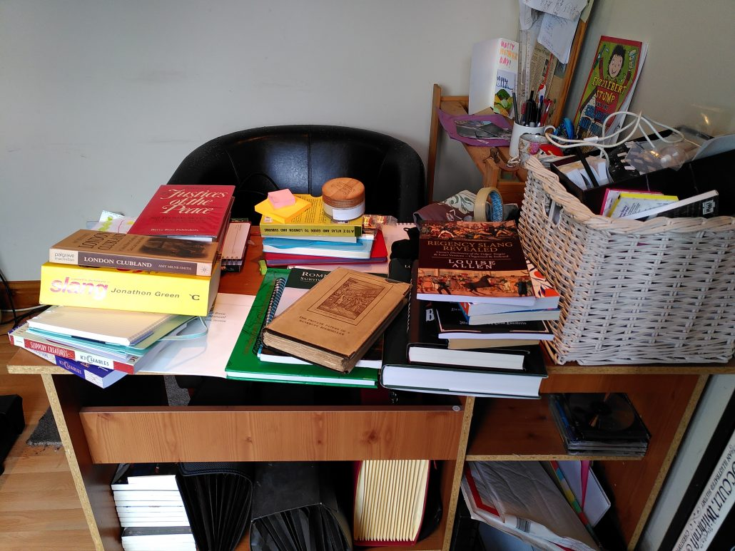 Desk absolutely covered in books and crap
